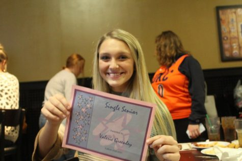 "Senior, Valerie Greenley, holding up her ""single senior"" award."