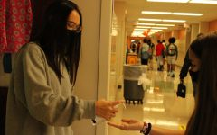 Freshman Allison Gosling squirts hand sanitizer into her classmate's hand before they enter the classroom.