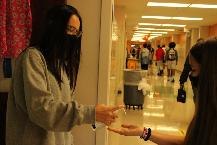 Freshman+Allison+Gosling+squirts+hand+sanitizer+into+her+classmate%27s+hand+before+they+enter+the+classroom.